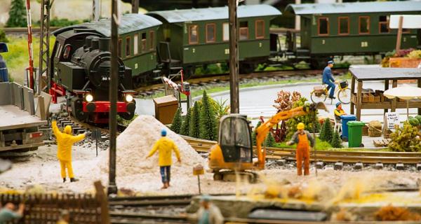 Makieta miniatury kolejki parowej na placu budowy, dookoła wydają się krążyć małe ludziki, na środku makiety pracuje koparka