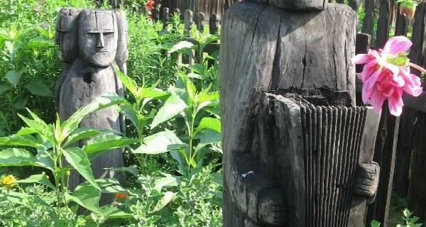 Drewniany posąg przedstawiający chłopa trzymającego naczynie, posąg uproszczony, nieszczegółowy w Sieradzkim Parku Etnograficznym