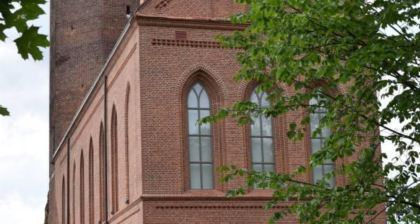 Gmach Regionalnego Muzeum w Człuchowie widziany z boku, ceglana konstrukcja osłonięta częściowo drzewami, z tyłu widać kawałek wieży