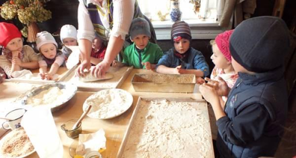 zajęcia z wypieku i ugniatania ciasta, Pani ugniata kawałek ciasta, dzieci ustawione dookoła oglądają całą sytuację