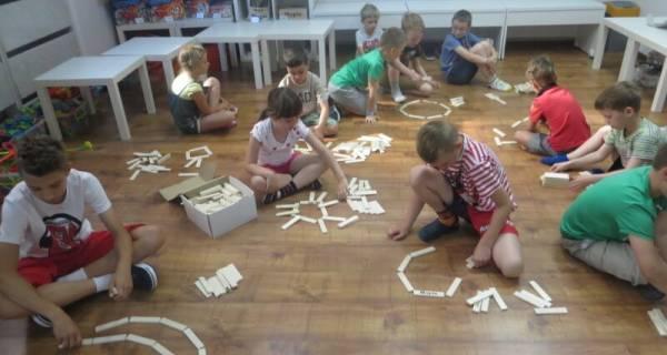 Dzieci bawią się budując z klocków swoje konstrukcje