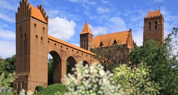 Most z korytarzem zamku w Kwidzynie, przesłonięty białymi kwiatami