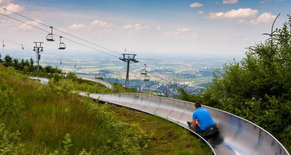 Chłopak w niebieskiej koszulce zjeżdżający po zjeżdżalni