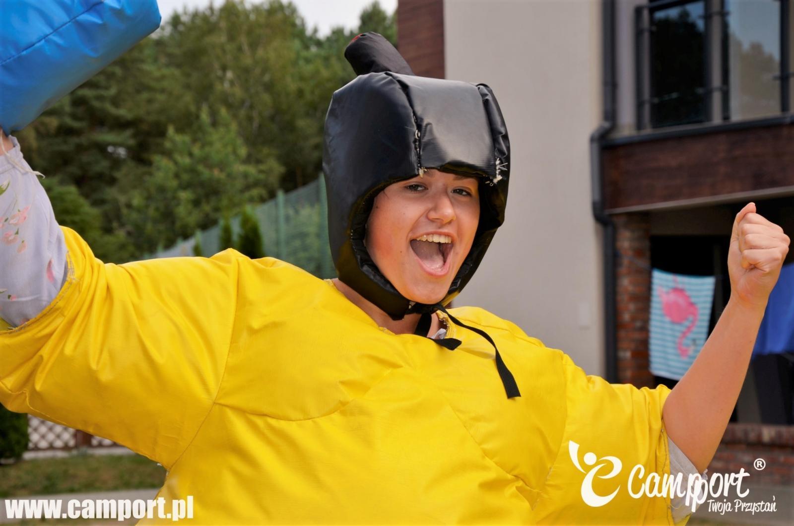 Dziewczyna ubrana w gruby żółty strój imitujący masę sumity, wykonuje gest zwycięstwa unosząc ręce do góry